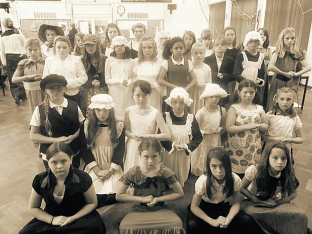 This Is Wiltshire: Westbury Juniors in their Victorian outfits learn how to sit still and quiet, hands clasped