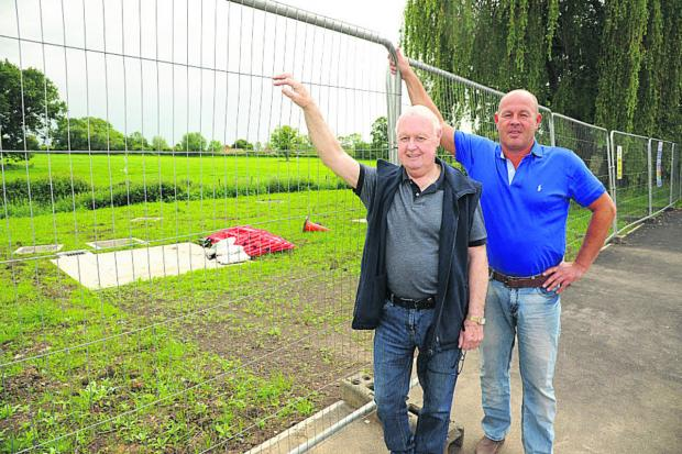 This Is Wiltshire: Brookmead residents Eamonn Doyle and Paul Weightman are concerned about the way the play area was left by Wessex Water