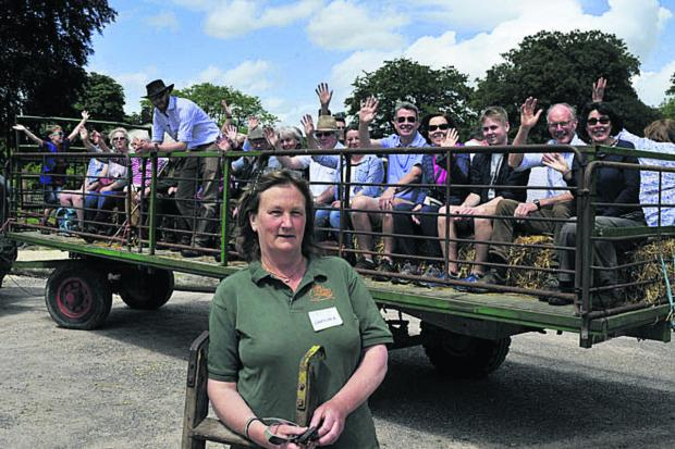 This Is Wiltshire: Caroline Wheatley-Hubbard and her son Christopher with a trailer-load of visitors about to set off on their  tour of Boynton Farm, near Warminster