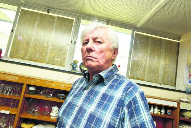 This Is Wiltshire: Peter Mallinson with the boarded up windows of Walcot charity shop and library behind him