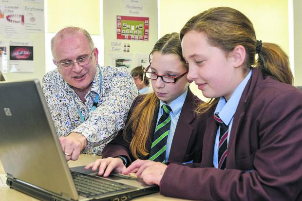 This Is Wiltshire: Playwright Mark Wheeller passes on his tips to Shauna and Maddison as they work on an English assignment