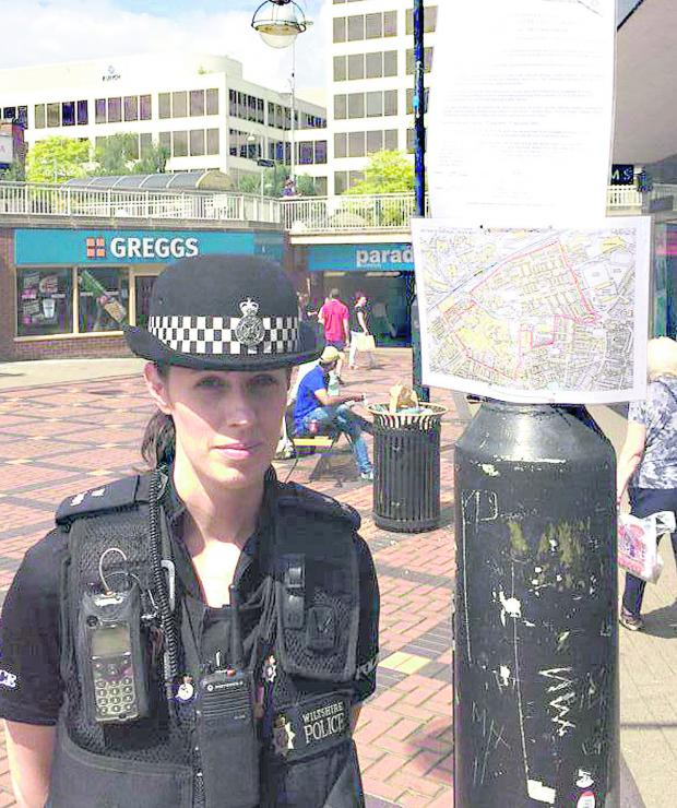 This Is Wiltshire: PCSO Emma Millarvie with a dispersal order sign in the town centre