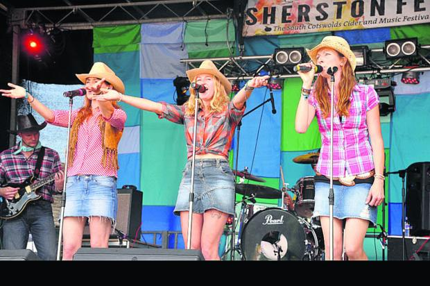 This Is Wiltshire: Members of the Sherston Village People perform in stetsons at Sherstonfest. Pictures by Vicky Scipio