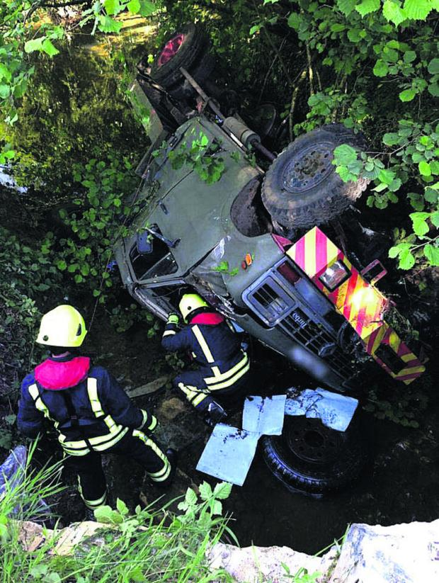 This Is Wiltshire: Firefighters at the cab of the truck which crashed at Radford near Calne last night