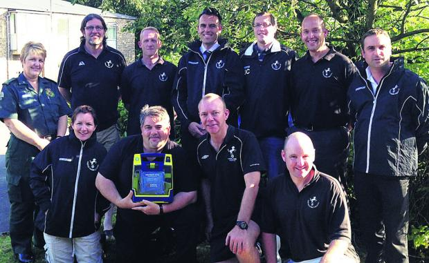 This Is Wiltshire: Colts secretary Trevor Newman and chairman Jon Clark (front, centre) with the South Western Ambulance Service Trust's Julia Doel and coaches and committee members