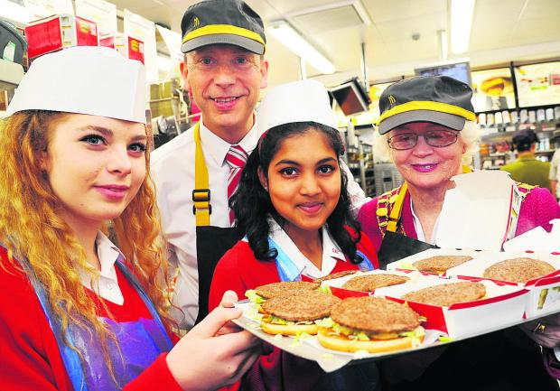 This Is Wiltshire: Student Taylor, Paul Booth, the franchisee of McDonalds, student Astria and mayor Teresa Page making burgers at McDonalds, in Great Western Way