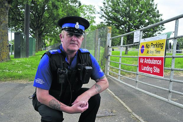 This Is Wiltshire: PCSO Shaun Redmond beside the often obstructed Wiltshire Air Ambulance access gate to the playing fields
