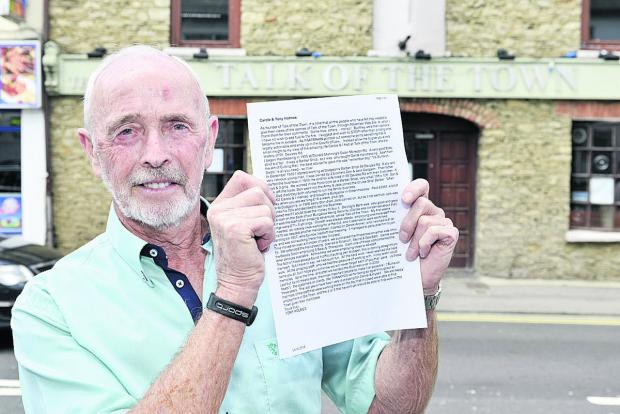 This Is Wiltshire: Tony Holmes outside the closed Talk of the Town salon holding his open letter
