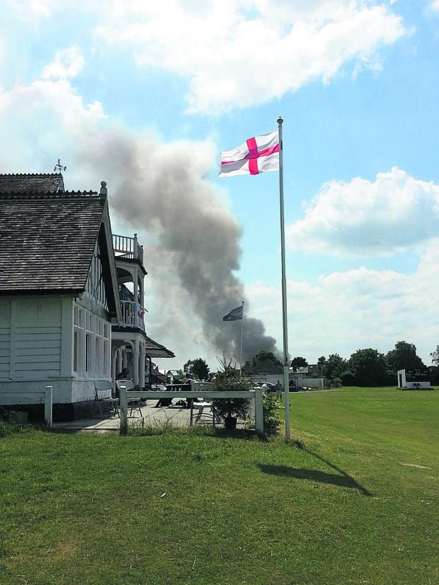 This Is Wiltshire: The scene of the smoke this afternoon from Trowbridge Cricket Club, where the game went ahead unaffected
