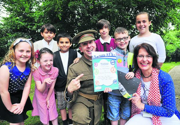 This Is Wiltshire: Indy Mark Andrews, third right, receives his award from actor David Cooper and school eco travel  coordinator Avril Brown, surrounded by pupils, from left, Grace, Bethany, Zak, Adam, Ewan and Lauren