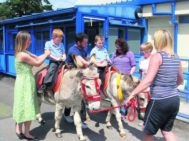 This Is Wiltshire: The children from Robins class enjoy a ride around the playground at Larkrise School
