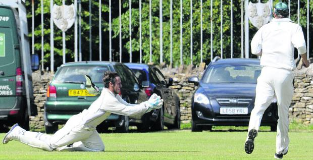 This Is Wiltshire: Corsham wicketkeeper Steve Bullen goes full length to take a catch during his side's victory over Frocester on Saturday