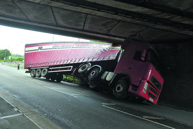 This Is Wiltshire: The lorry stuck under Wootton Bassett Road bridge yesterday. Picture: THOMAS KELSEY