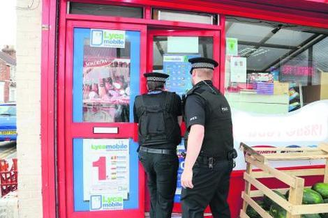 This Is Wiltshire: Police enter a shop in Manchester Road, when Swindon police and Trading Standards teamed up with Smokefree South West in the hunt for illegal tobacco