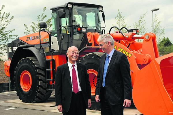 This Is Wiltshire: Kazuya Miura, president and chief executive officer of Hitachi Capital Corporation, with Jon Lawes, managing director of Hitachi Capital Commercial Vehicle Solutions and an Hitachi 27-tonne construction vehicle. Picture by Trevor Porter