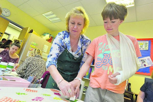 This Is Wiltshire: Cowshedstudio founder Sue Green helps young patient Russell with art for the mural