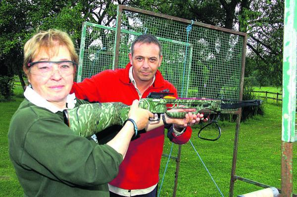 This Is Wiltshire: Linda Reed gets some help with a crossbow from Dave Mugglestone at the fundraising sports day