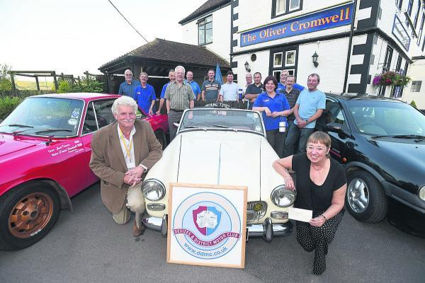 This Is Wiltshire: Air ambulance volunteer Jim Luff receives the cheque from motor club secretary Janet Edwards at the Oliver Cromwell. Picture by Diane Vose