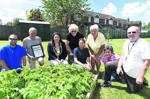 This Is Wiltshire: Residents and community garden committee members in front of their Waiblingen Way garden, Darren Pickford, Richard Arnold, mayor Sarah Bridewell, Sue Bryant, Carol Pickford, Val King, Coun Jane Burton and committee chairman Ray Snell
