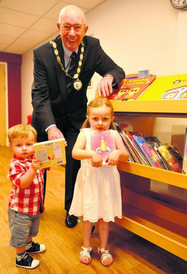 This Is Wiltshire: Parish council chairman John Foley at Grange Leisure Centre's new library with  Oliver and Ava Godwin