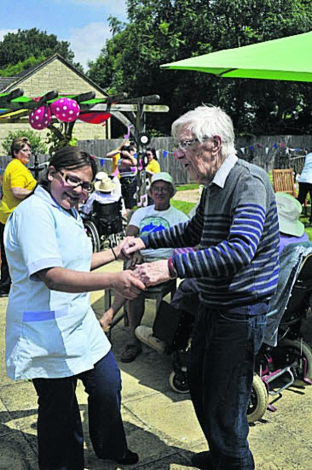 This Is Wiltshire: Wingfield Care Home resident Dr Michael Thomas dancing with carer Aziza El-Filali