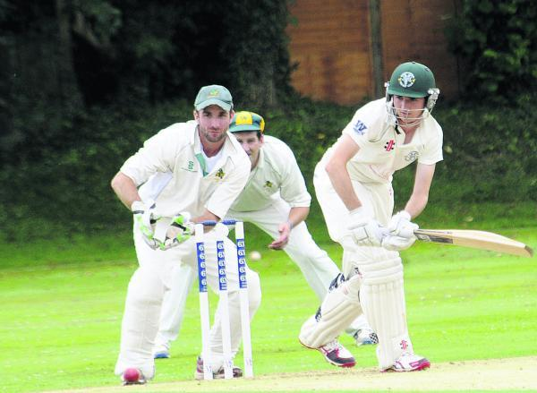 This Is Wiltshire: Warminster wicketkeeper Dave Bateman watches as Rockhampton's Guy Brothwood bats