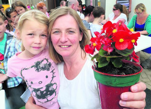 This Is Wiltshire: Scarlett, 7, and her mother Kate South with a plant grown by pupils at St Mary' s School, Purton