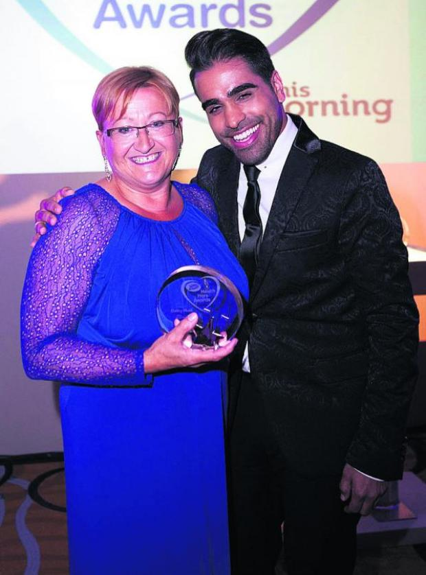 This Is Wiltshire: CBeebies and Watchdog specialist Dr Ranj Singh hands the Boots Health Hero Award to Wiltshire nurse Carol Bennett