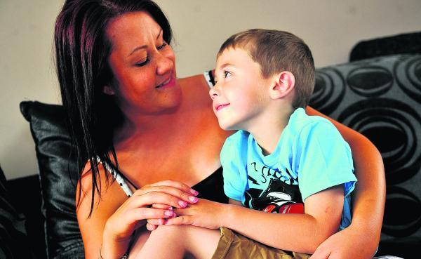 This Is Wiltshire: Jack Pike, who is now able to walk unaided six months since his operation, pictured with his mother Kylie