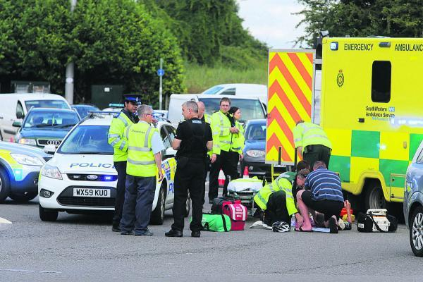 This Is Wiltshire: A man is treated in the road by paramedics at Bruce Street Bridges, Swindon