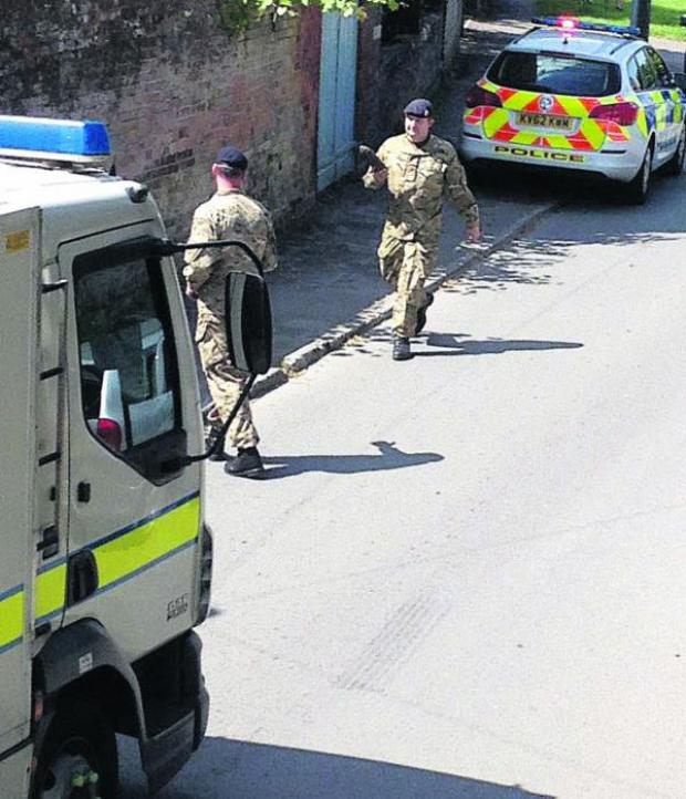 This Is Wiltshire: Bomb disposal officers remove the spent artillery shell from Urchfont yesterday