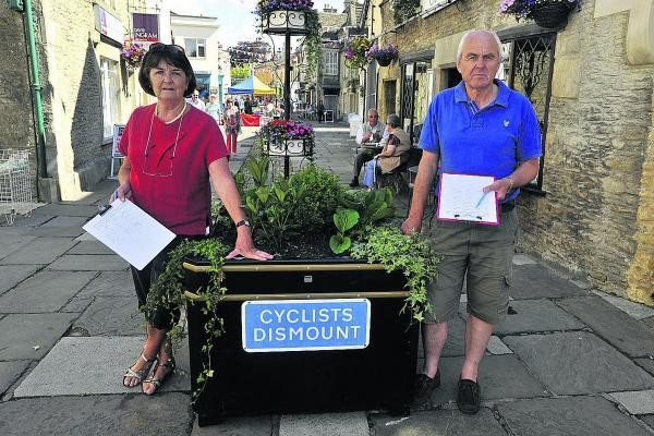 This Is Wiltshire: Christine Reid and Humphrey Barnikel pictured by one of the offending signs in the High Street