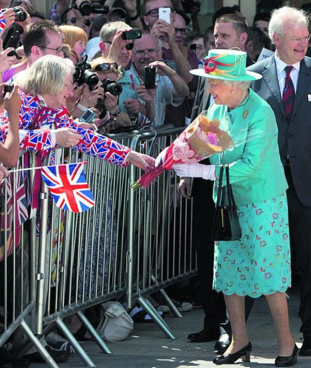 This Is Wiltshire: A fan presents the Queen with flowers at Reading station today. Picture by Steve Parsons/PA Wire