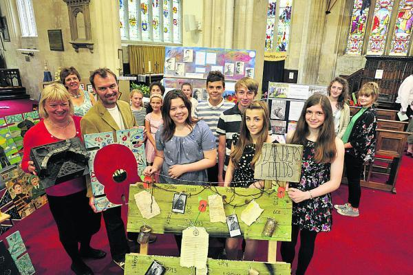 This Is Wiltshire: Work to remember those who fought and died in the First World War carried out at eight Trowbridge Schools was displayed in St John's Church. Pupils and organisers are pictured with some of the various displays. Picture by Glenn Phillips