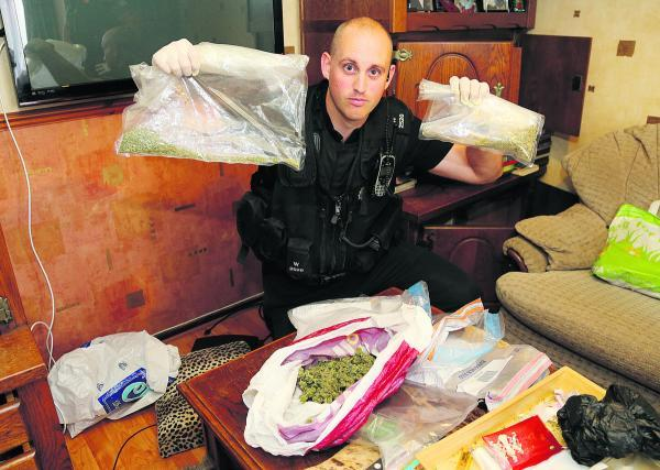 This Is Wiltshire: PC Gary Bracey with some of the cannabis found during a drugs raid on a house in West Swindon