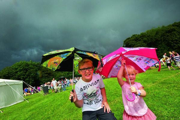 This Is Wiltshire: Joshua and Maisey wait for the storm to pass at Stratton Festival on Saturday