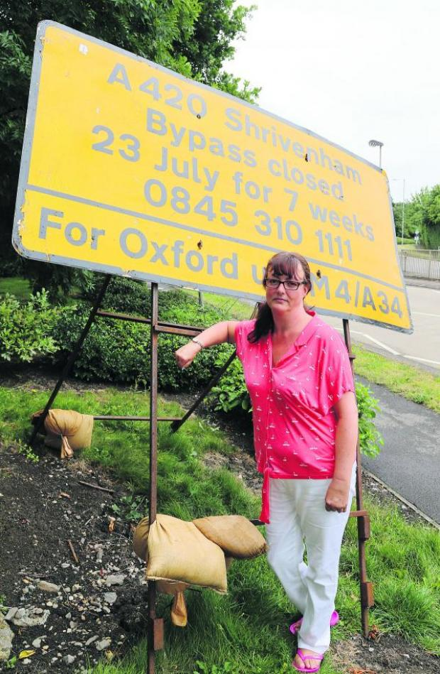 This Is Wiltshire: Shrivenham Parish councillor Sarah Day pictured at a sign warning drivers about the closure of the A420 between Swindon and Oxford for seven weeks starting tomorrow