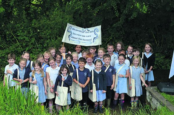 This Is Wiltshire: Pupils from Preshute Primary School celebrate the release of eels into the River Kennet