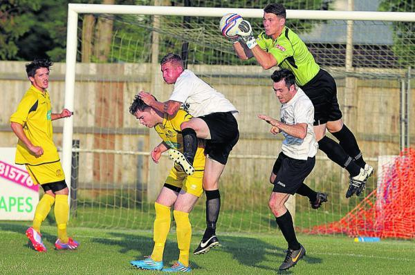 This Is Wiltshire: Chippenham Town goalkeeper Kent Kauppinen gathers with defenders Greg Tindle and Toby Osman and Calne's Neurin Jones (white, left), Tom Slater (white, right) close by during Tuesday's friendly (Pictures by Chippenham Town FC)