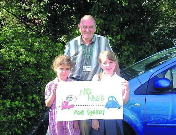 This Is Wiltshire: Coun Bill Douglas with, left, Kya Heathcote, seven, from Charter School, and Ellie Purdy, nine, from King's Lodge School, joint  winners of a poster competition who will have their design used as the town banner for the No Need for Speed campaign