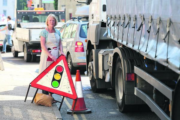 This Is Wiltshire: Judy Hurt, the owner of the Christmas shop in Lechlade, is angry about the traffic problems in the town due to the roadworks on the A420 Swindon to Oxford Road