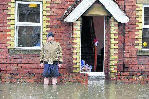 This Is Wiltshire: A Dursley Road resident watches the flood waters rise outside his home on Saturday. Picture by Glenn Phillips