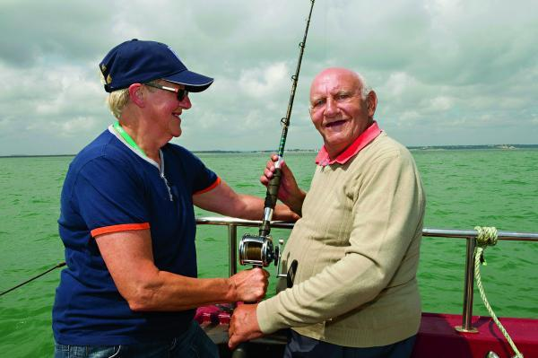 This Is Wiltshire: Nicky Blick, activity organiser at Whitbourne House Carehome, Swindon, with resident Brian Davis on a boat just off the south coast in Studland Bay