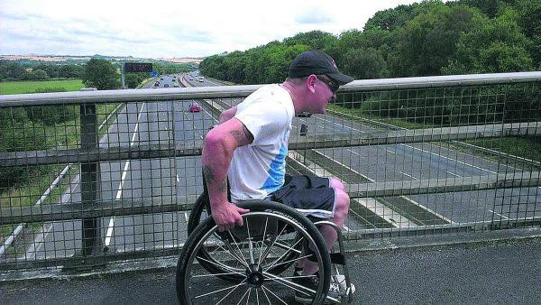 This Is Wiltshire: Martin Lane crosses the M4 near Swindon during his marathon effort