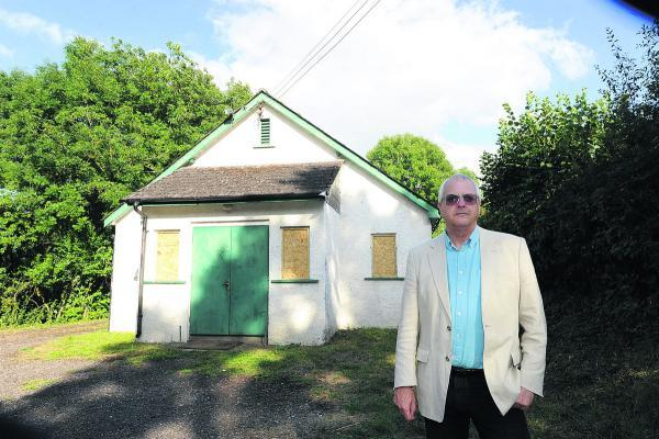 This Is Wiltshire: Parish councillor Nick Greene outside the vandalised Stanton St Quintin hall. Picture by Paul Morris