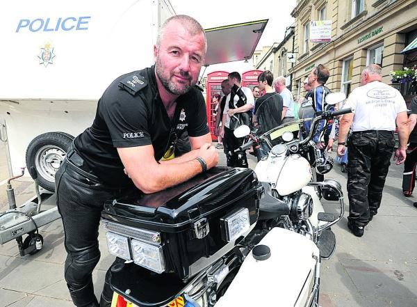 This Is Wiltshire: Sgt Craig Hardy with a police Harley-Davidson at the annual Calne Bike Meet. Picture by Paul Morris