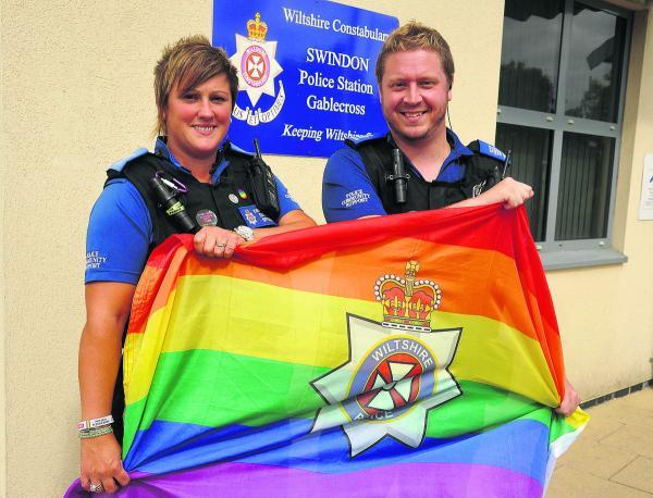 This Is Wiltshire: Kate Jason-Collier and Lee Hare with the rainbow flags which will be flown from Gablecross police station and Devizes HQ in support of the Pride event