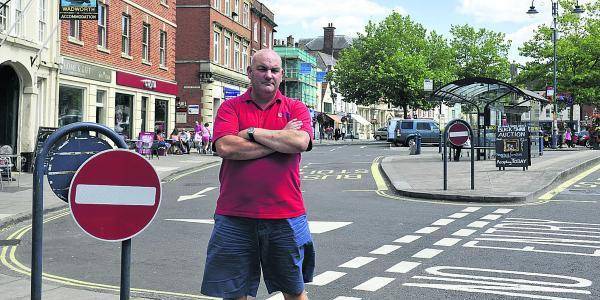 This Is Wiltshire: Neil Fautley is angry about cars using the one way only road the wrong way outside his shop
