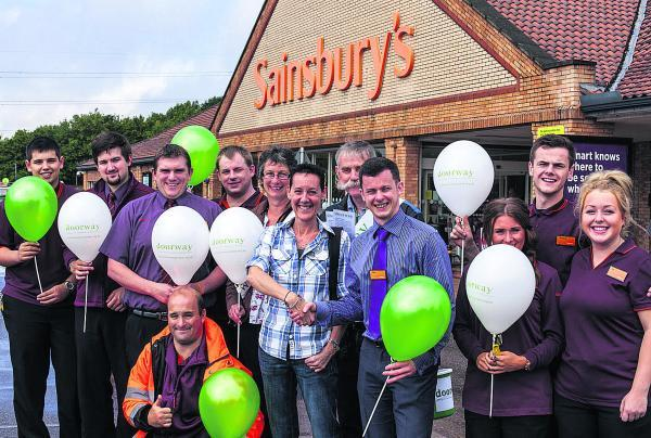 This Is Wiltshire: Doorway director Lisa Lewis with Sainsbury's duty manager Dan Hulland, staff and the charity's volunteers