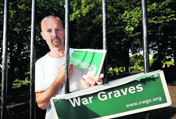 This Is Wiltshire: Mark Sutton, of the Swindon in the Great War group, is upset that the Commonwealth War Graves sign at Radnor Street Cemetery has been vandalised